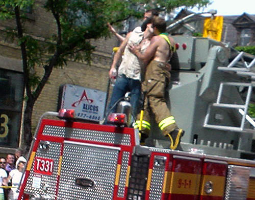 Shirtless fireman in suspenders and turnout pants plants a kiss on man in cowboy hat atop a firetruck