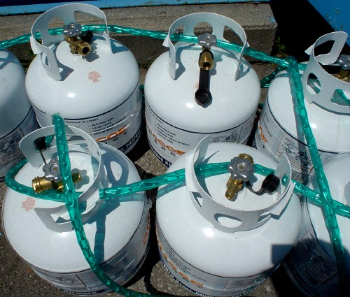 Seven white propane tanks sit on the ground lashed together by a chain covered in bright-green plastic