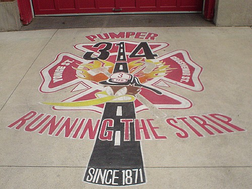 Appliqué on driveway in front of red rollup door shows a Road Runner–like mascot in a fire helmet driving on a road running through a four-leaf clover. Two of the leaves read YONGE ST. and GROSVENOR ST. Legend reads PUMPER 314 RUNNING THE STRIP SINCE 1871