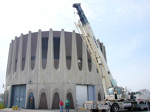 Circular building with V-shaped concrete flutings sits behind a giant crane that raises its hook