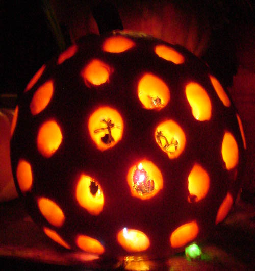 Pumpkin has carved round holes across its entire surface and lights within