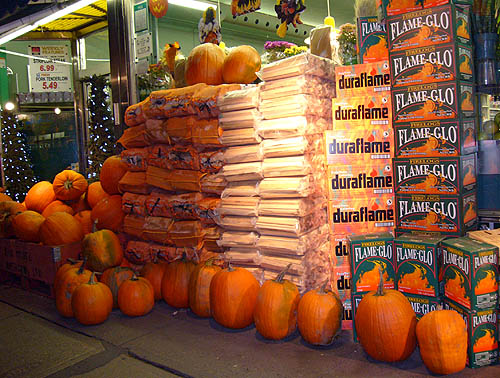 Large pumpkins and ten-foot-tall piles of orange, beige, and green firelogs outside a store