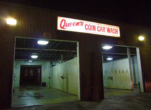 Sign over two car bays reads Queen's Coin Car Wash, with Queen's in cursive