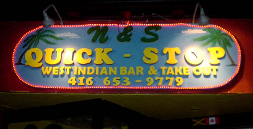 Illuminated sign with raised wooden sign reads N&S QUICK-STOP WEST INDIAN BAR & TAKE OUT in Cooper Black and Brush Script
