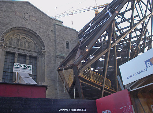 Giant criscrossing metal girders explode like a pyramid off the roof and across the face of an old stone building