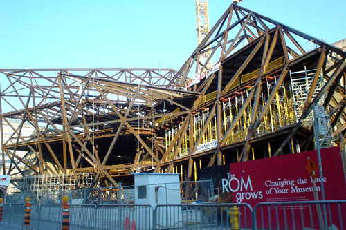 Sign reads 'The ROM grows' in front of three storeys of steel trusses pointing triangularly out from a central meeting point