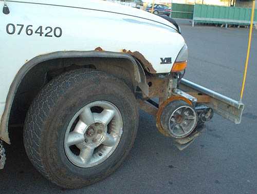 White pickup truck has a wide metal wheel half the diameter of the truck's wheel that sits behind it