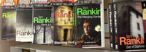 Sequence of Ian Rankin paperbacks on a rack, with author's name in bright Helvetica letters