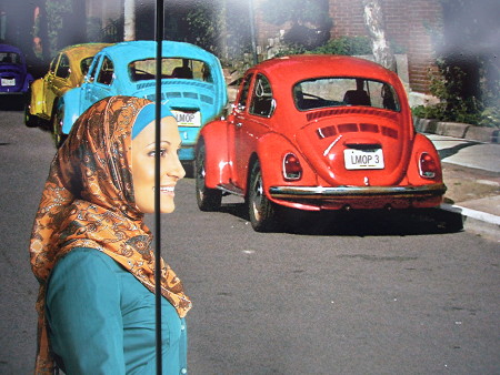 Close-up of photo of Rayyan from 'Little Mosque' crossing a street where two old Beetles are parked