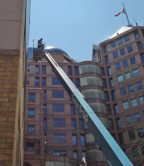 Man stands in gondola in midair on the end of a huge blue metal arm (labeled Genis S-60) an arm's reach from a brick building