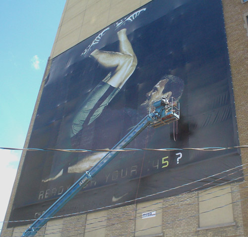 Long metal arm holds metal gondola close to a three-storey banner showing a man in T-shirt and Lycra shorts pressing his feetup to the top edge