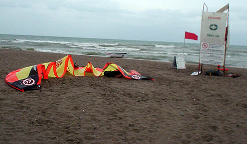 Overcast beachfront scene has empty lifeguard station alongside a red flag and a collapsed parasail