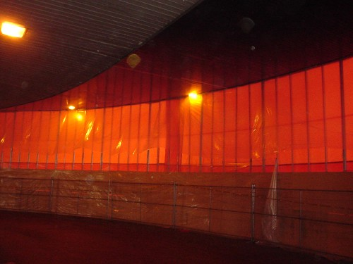Windows wrapping around a bus bay glow orange from the plastic batting that covers them