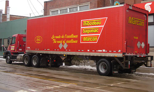 Red truck has yellow lettters on an even redder trapezoidal background that read Thibodeau Saguelac Marcan