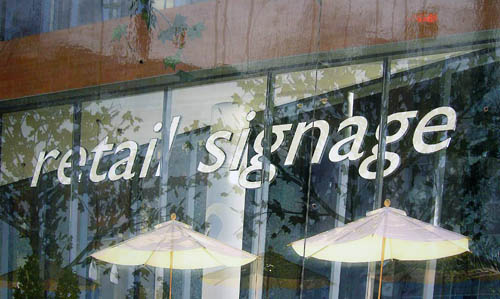 Words on glare-obscured vitrine read retail signage in Gill Sans