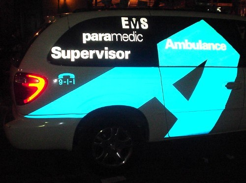 In reflected light at nighttime, decals on a van show the words 'EMS Paramedic Supervisor' and a huge blue letter A