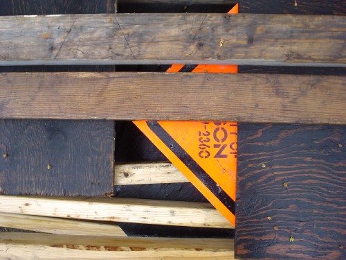 Fragment of orange traffic sign peeks through a covering of planks and black boards