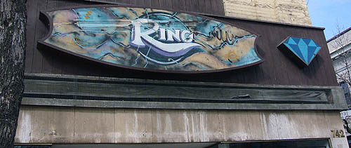 Cartouche-shaped sign with background of brown landscape with bluish seas has the word Ring in a blue circle, with a diamond in a separate unit on the right