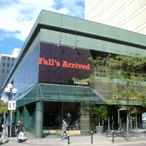 Sign on green Harry Rosen store reads 'Fall's Arrived' in orange Rockwell type