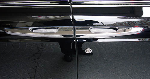 Silver door handles on black car have inner edges facing each other at the gap between the doors