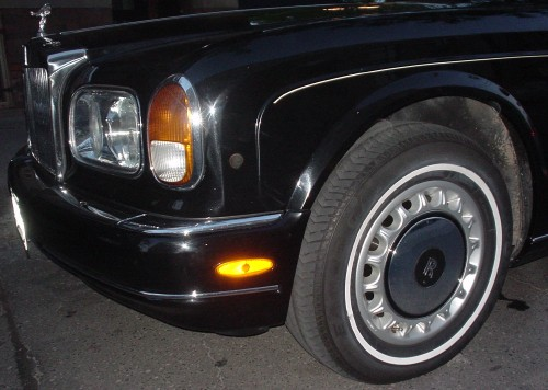 Front-left  silver wheel and massive tire of parked black Rolls-Royce