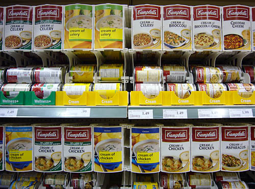 Display cases have row upon row of model soup-can labels atop actual dispensers of soup cans