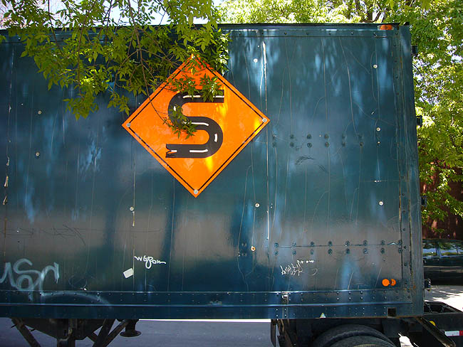 Mottled teal transport trailer is emblazoned with a sign resembling a road sign – an S inside an orange triangle