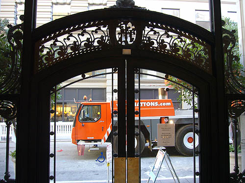 Giant orange crane cab silhouetted behind decorated wrought-iron doorway
