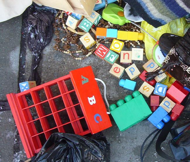 Alphabet blocks sit discarded amid a junk pile