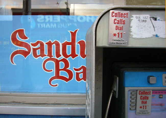 Payphone with English/Spanish stickers partially obscures a sign in blackletter type: Sand Ba