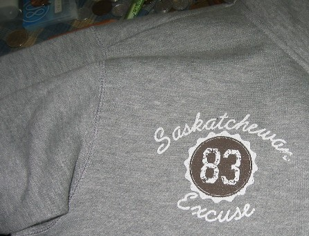 Grey sweatshirt is emblazoned 83 Saskatchewan Excuse