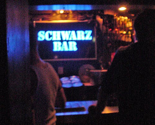 Dark photo shows two guys at a bar whose bright blue sign reads SCHWARZ BAR in stenciled letters