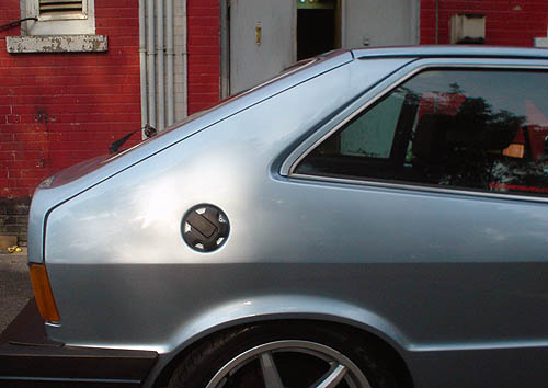Rear third of a Silver late-'80s Scirocco against red-brick wall