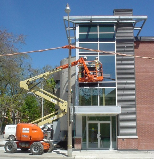 Orange scissor lift to the left of a steel-and-glass building zigzags two guys up to the third storey much further to the right
