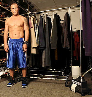 Shirtless Sean Avery, wearing excessively long blue nylon shorts and standing near a clothes rack on wheels