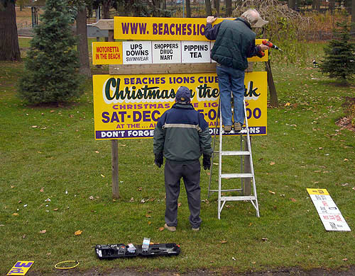 Two men use a ladder and power tools to post a set of yellow billboard segments for 'Beaches Lions Club Christmas in the rk""