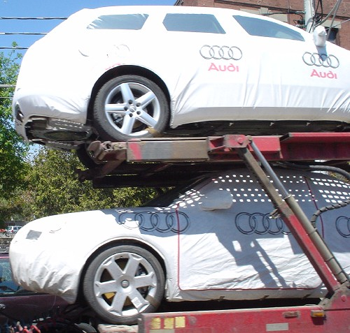 Audi A3s sit on auto carrier completely covered in white film emblazoned with 'Audi' and the four rings
