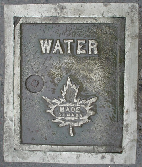 Brass plate with steel border reads WATER, with WADE CANADA inside a maple leaf