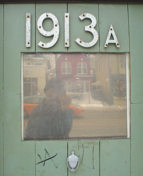 Scuffed green door contains a mirrored window, a steel knocker, and metal letters reading 1913A