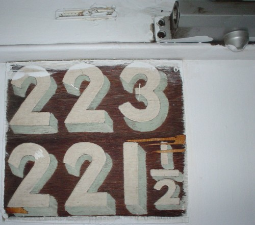 Below a hydraulic door closer, a cracked wooden sign has handpainted numbers: 223 on top, 221½ below