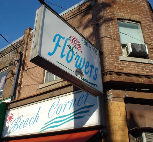 Sign on building reads 'Beach Corner' in mid-century script; sign hanging from building reads 'Flowers' in scrunched Zapf Chancery