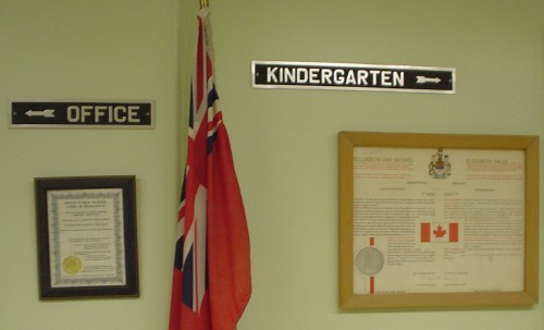 Canadian flag stands at rest between two framed certificates on a wall and thin, old-style metal signs reading ← OFFICE and  KINDERGARTEN →