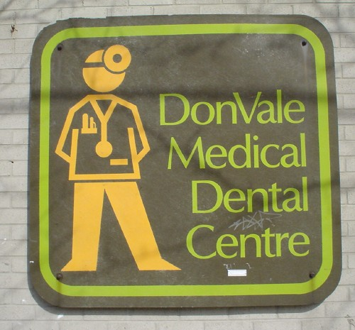 Sign reads DonVale Medical Dental Centre in chartreuse-coloured Optima. Figure of a man in yellow, complete with stethoscope, pen-filled pocket, and mirrored magnifier cap, stands to the left
