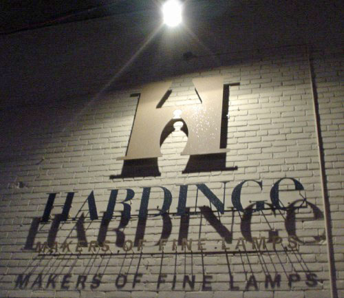 Letters projecting from brick wall cast shadows under a bare bulb and read 'Hardinge Makers of Fine Lamps'
