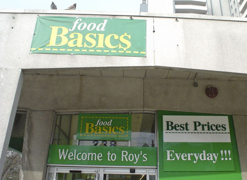 Green signs tacked up on door transom and concrete lintel read food Basic$, Welcome to Roy's, Best Prices Everyday!!!