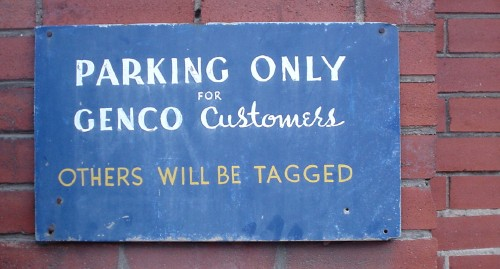 Hand-lettered sign in white and yellow upper case and script type reads 'PARKING ONLY FOR GENCO Customers' and 'OTHERS WILL BE TAGGED'