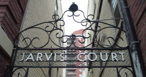 Ornate wrought-iron transom is labeled with JARVIS COURT in steel letters