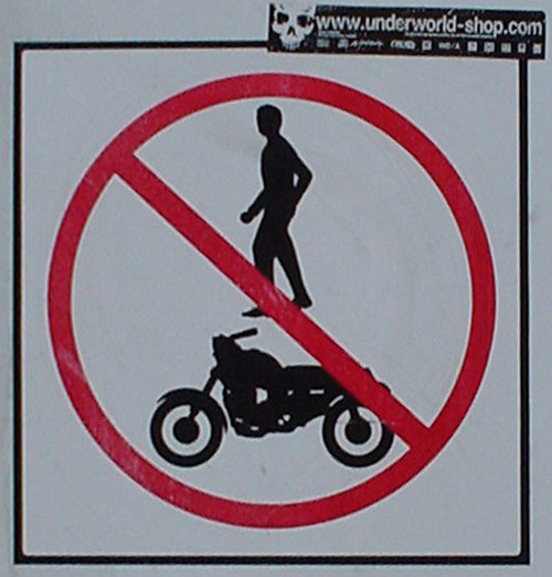 Sign shows bar dexter through figure of a man hovering over a motorcycle
