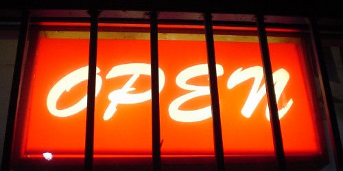Glowing orange sign behind metal bars reads OPEN in Brush Script capitals