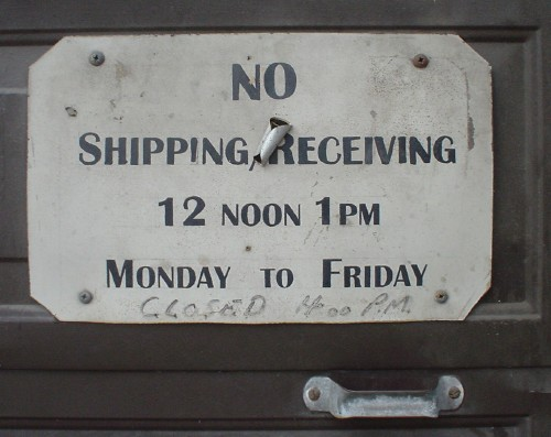 Sign with sticker applied haphazardly in the middle reads 'NO Shipping, Receiving 12 noon 1pm Monday to Friday' in small caps, with 'Closed 400 P.M.' handwritten in faded marker